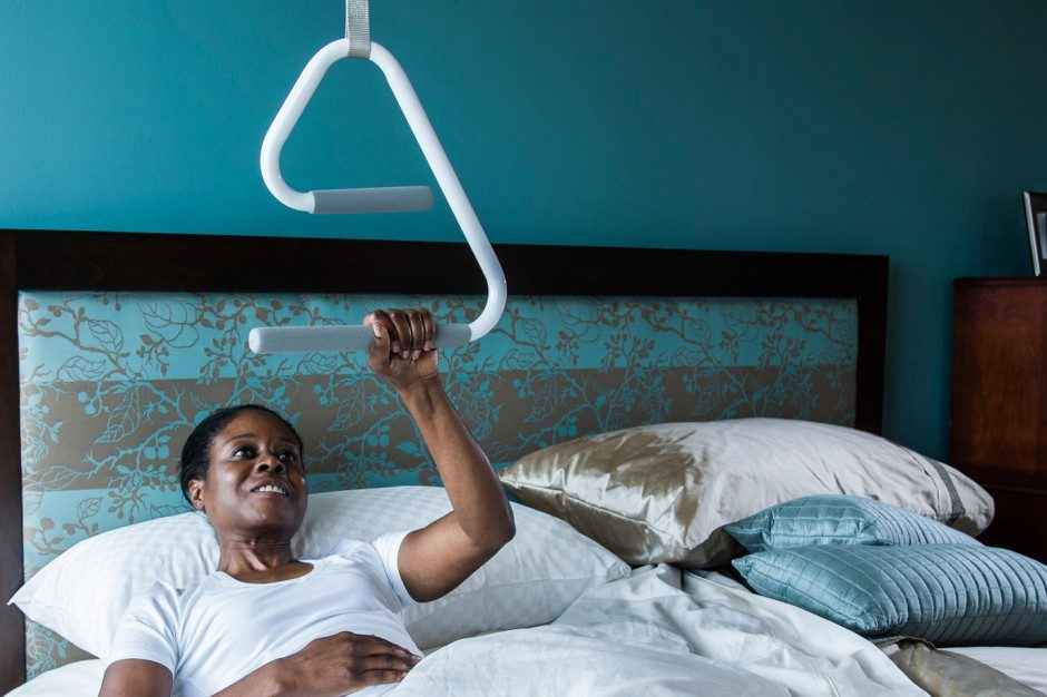 Photo of a woman in bed using an overhead trapeze to lift herself into an upright position.